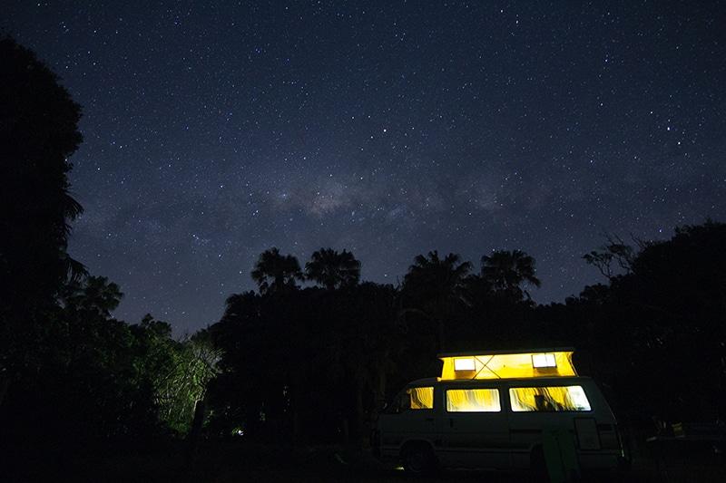Sfeerbeeld van een camping bij nacht waarbij een caravan accu wordt gebruikt voor licht